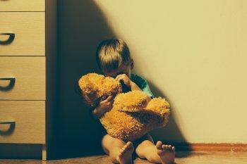 Sad boy sitting down, hugging teddy bear